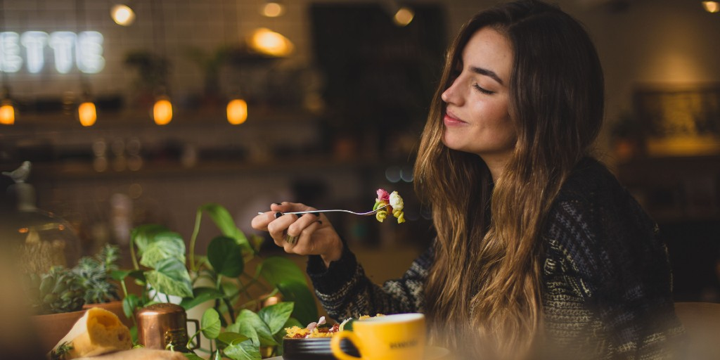Girl smiling serenely holding a fork with pasta