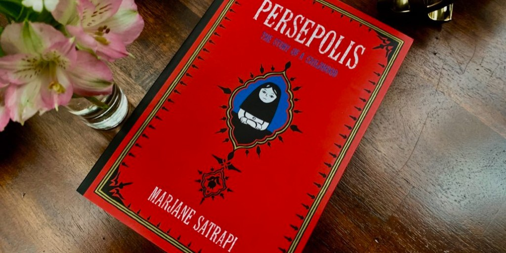 A copy of 'Persepolis' - featuring a red cover with a young girl wearing a dark headscarf and looking unhappy - lies on a wooden surface by a vase of flowers.
