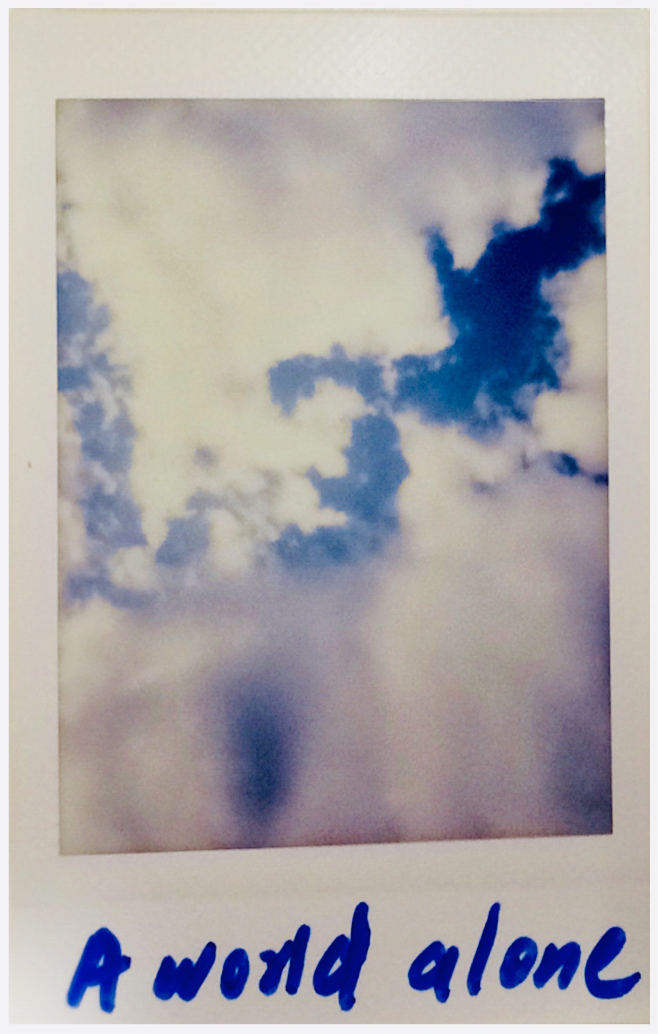 A polaroid of a cloudy blue sky with the words a word alone scribbled at the bottom.