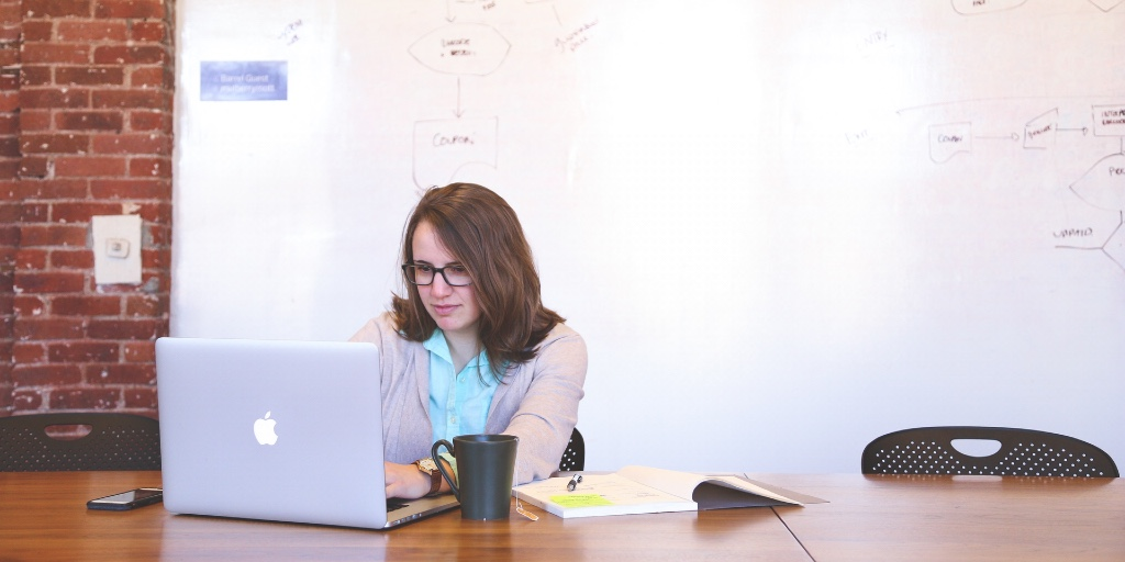A white, brown-haired woman sits at a conference table. She is working on her laptop and dressed smartly. Behind her is a brainstorming map on a whiteboard. Around her, on the table, is an open book, her phone and a mug of tea.