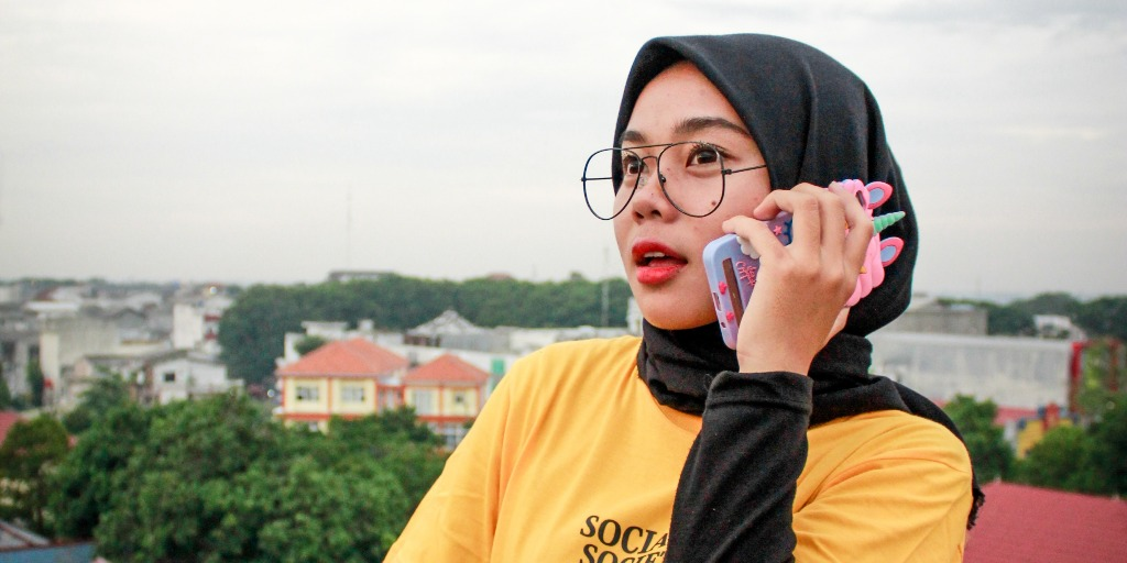 A brown woman talking on the phone. She is wearing glasses and a scarf and her eyes are looking ahead in the distance.