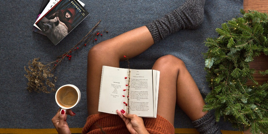 A book rests open on a woman's lap with a small branch holding open the page. The woman is holding a mug of coffee and wears an orange sweater dress and grey socks. Her nails are painted red. She is seated on a grey blanket and a small bouquet, wreath, and a pile of books are scattered around her.