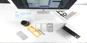 image description: a desk is seen from above with a desktop on it and a how to book along with sketches of a phone and a pencil