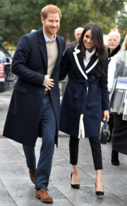 Meghan Markle, a dark-skinned woman with dark hair open, is smiling in a navy coat and black trousers, with her arm around Prince Harry, a red-haired man wearing a black coat, a cream jumper and blue trousers