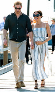 Meghan Markle, a dark-skinned woman with her dark hair pulled back, is wearing black sunglasses,a striped maxi dress with a thigh leg slit and brown sandals is smiling and holding hands with Prince Harry, a red-haired white man, wearing a dark shirt, beige trousers and black sunglasse