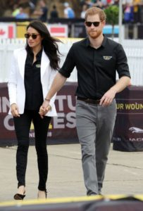 Meghan Markle, a dark-skinned woman with open dark hair, is wearing a white blazer, black shirt and trousers and brown sunglasses, is walking hand-in-hand with Prince Harry, a red-haired white man wearing a black shirt, grey trousers and black sunglasses