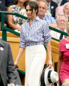 Meghan Markle, a dark-skinned woman with dark hair pulled back,is wearing a blue and white striped shirt, white wide-leg trousers and holding a white hat as she walked through arena stands