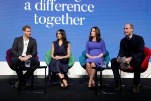 Meghan Markle, a dark-skinned woman with dark hair open, is sat down wearing a navy dress. To her right, Prince Harry, a red-haired man in a black suit and white shirt. To the left, Catherine Middleton, a pregnant woman in a blue dress, and Prince William, in a black suit]