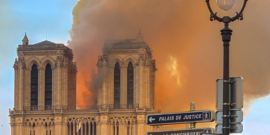 The cathedral of Notre Dame in Paris, engulfed in smoke and flames.