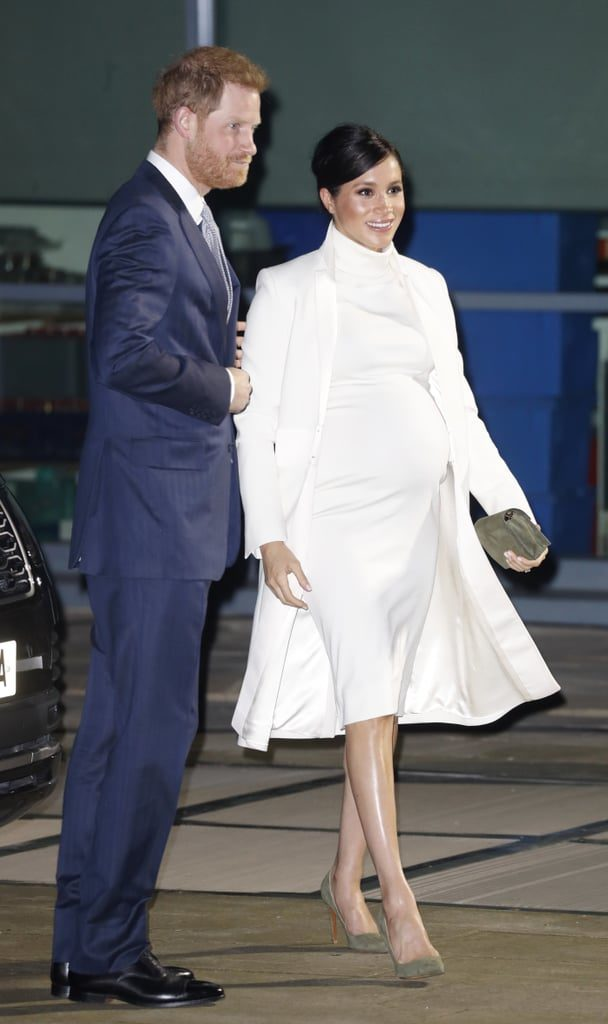 Meghan Markle, a brown-skinned woman with pulled-back dark hair walks in a white calf-length dress with a white coat. She is standing next to a white man with red hair in a navy suit.