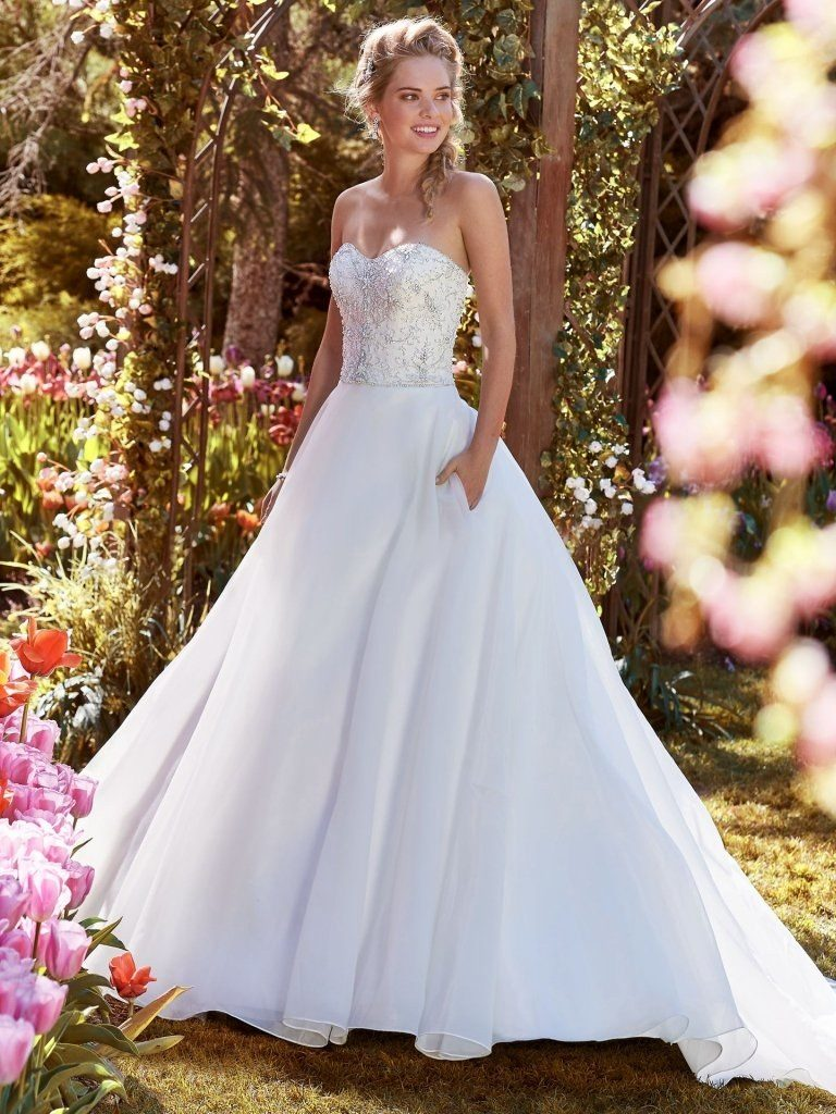 A white woman stands in a garden, wearing a white wedding dress. She has one hand in her pocket.