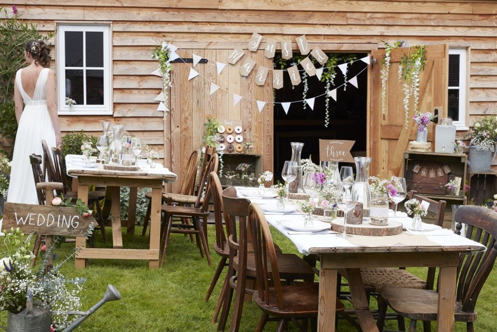A wedding is set up outside next to a barn, with wood tables and chairs and have a very rustic ambience.