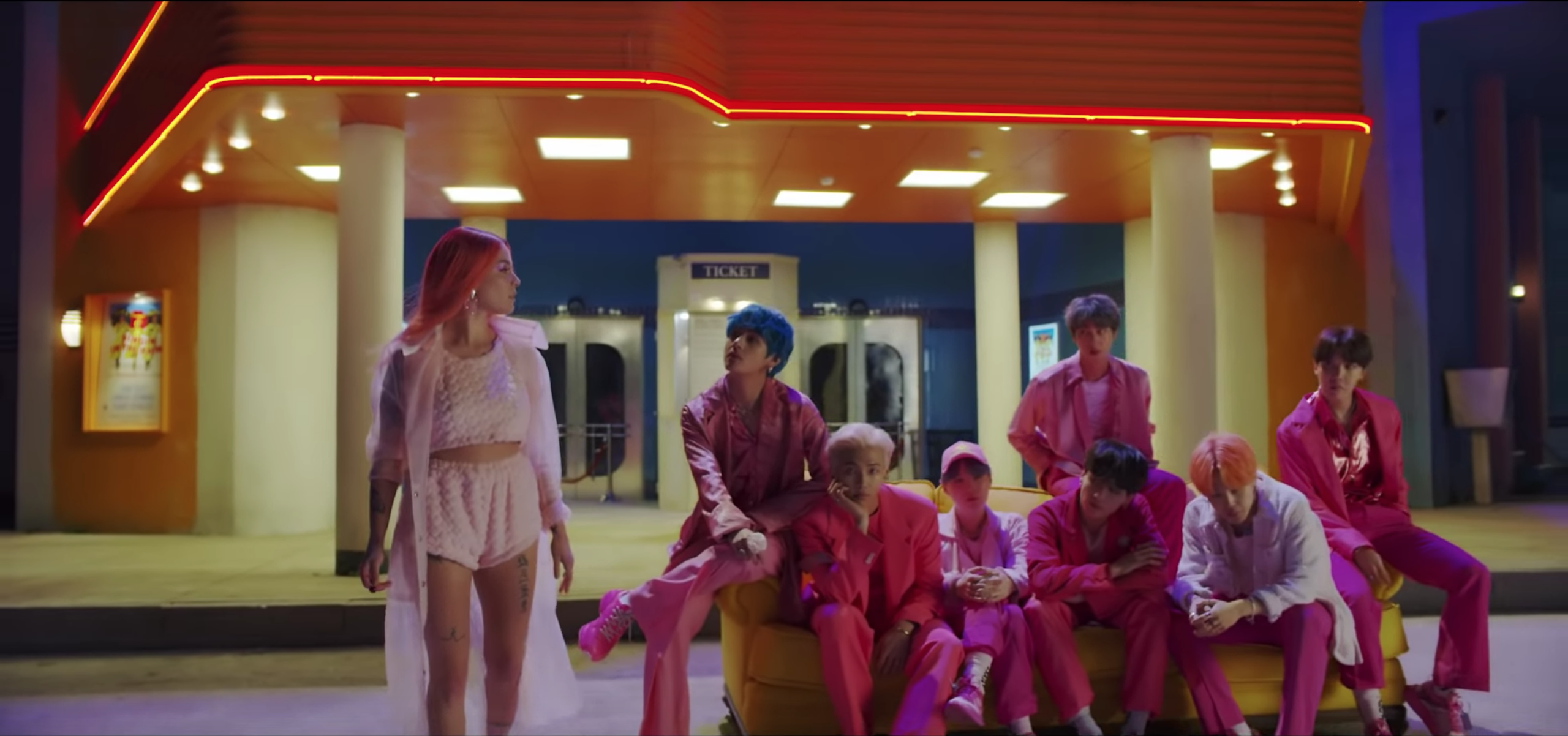 Seven member boy group BTS dressed in pink sitting on a bright yellow sofa looking at pop singer Halsey dressed in pastel pink the background is a building with a bright blue fluorescent sign that stays persona.