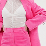 Body shot of a person wearing a hot pink corduroy suit with a white mesh top.