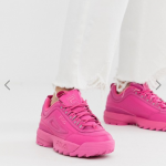 Shot of a model's feet wearing hot pink platform shoes and white denim jeans