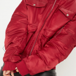 Picture of a burgundy bomber jacket with two pockets at the top and bottom