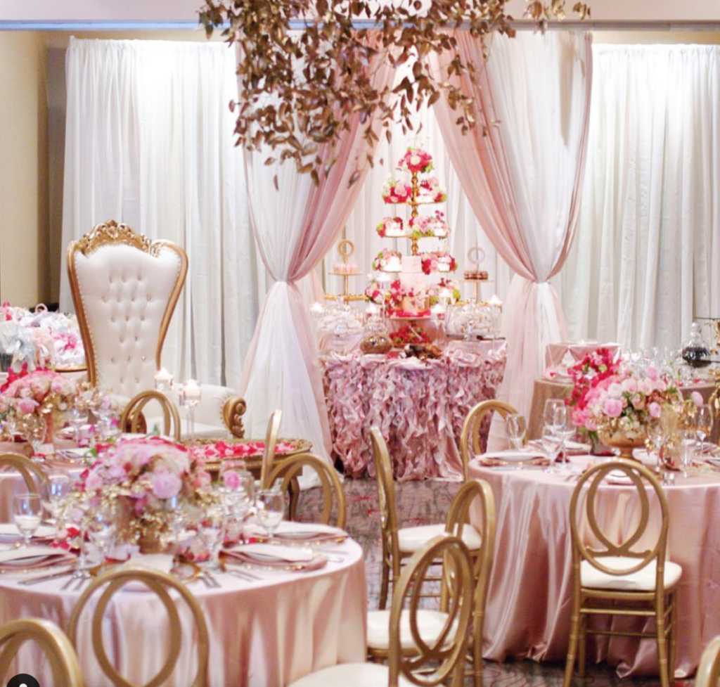 A hall is set up with pink themed flowers, gold chairs and a white backdrop.