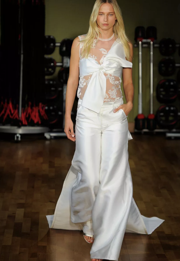 A white woman walks the runway, wearing a white wedding jumpsuit with with one hand in her pocket