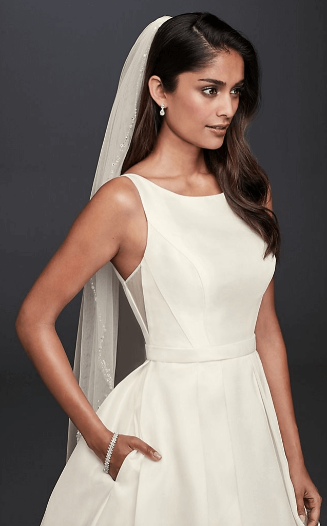 A woman wears an ivory wedding dress with her hand in her pocket.
