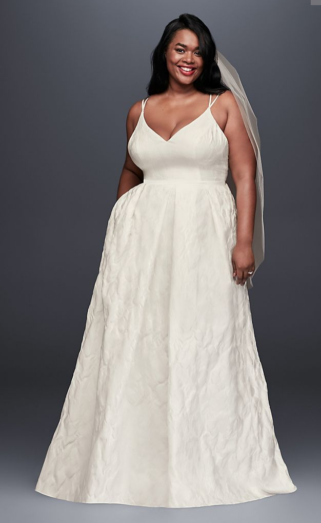 A plus size woman stands wearing an ivory wedding dress. She has one hand in her pocket