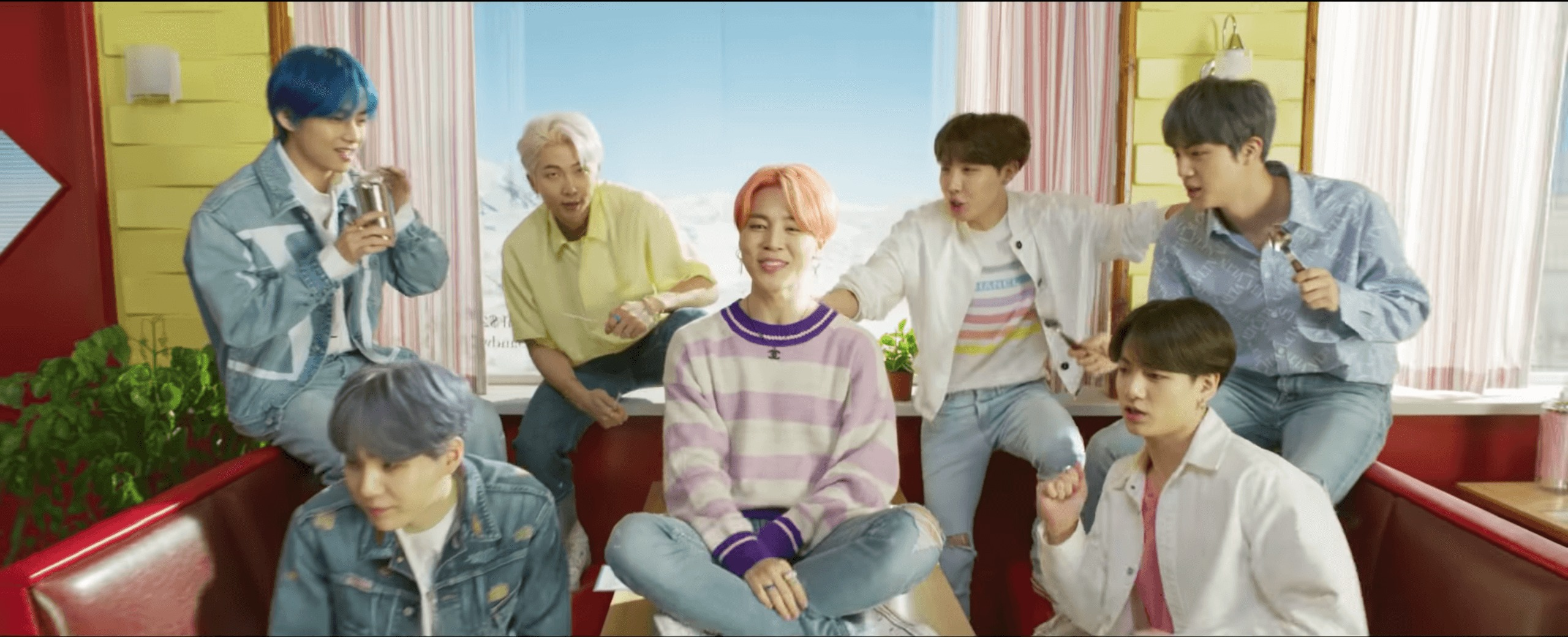 Seven member boy group BTS sitting around a Diner table while the boy with peach hair sits on the table in the center and smiles.
