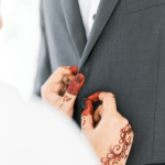 [Image description: A woman holds a man's tuxedo. Her hands are detailed with henna.] via Pexels