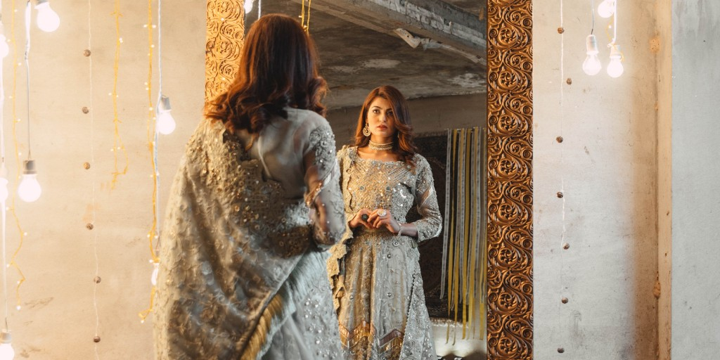 [Image description: Woman in bridal wear looks into a mirror.] via Pexels