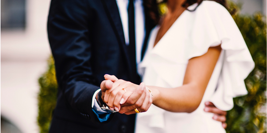 [Image Description: Couple holds hands during wedding.] Photo by Tiko Giorgadze on Unsplash