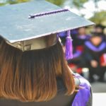 Image description: A girl wearing a graduation robe and cap is looking towards an out of focus crowd of students that are also wearing graduation outfits