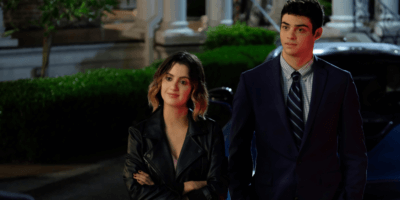 Celia and Books, stand in front of a car, she's wearing a pink dress underneath black leather jacket and he's wearing a blue suit.