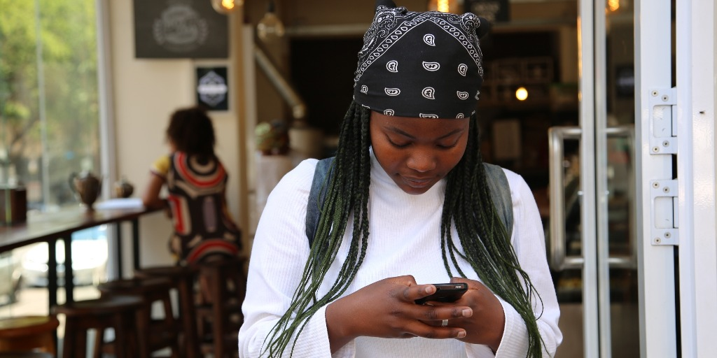 A woman wearing a black bandana looks down and types on her phone.
