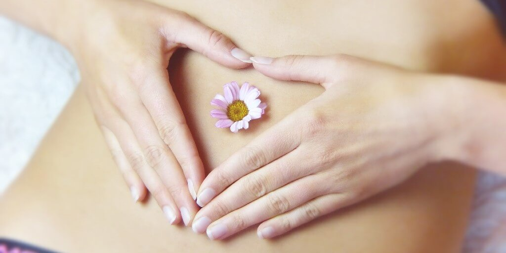 A white woman has her hands over her stomach in the shape of a heart with a white flower in the middle
