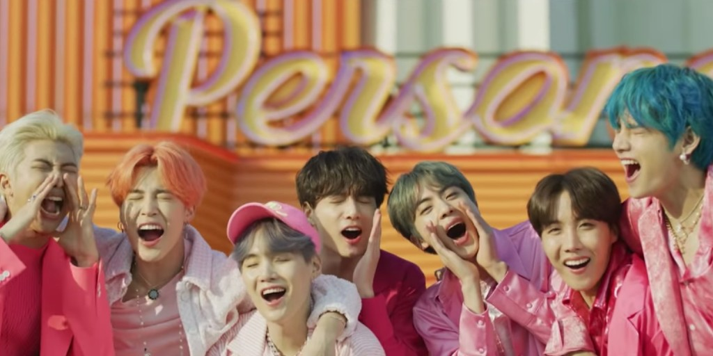 Seven members of the boy group BTS wearing various shades of pink and shouting with a sign behind them that reads persona.
