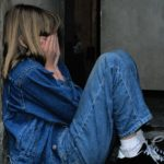 A blonde girl in a denim ensemble sits on a step with her back against a wall. Her knees are pulled in and her hands cover her face.