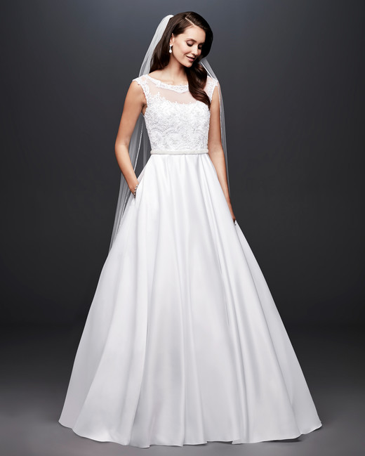 A white woman with dark hair wears a white wedding dress. She has one hand in her pocket.