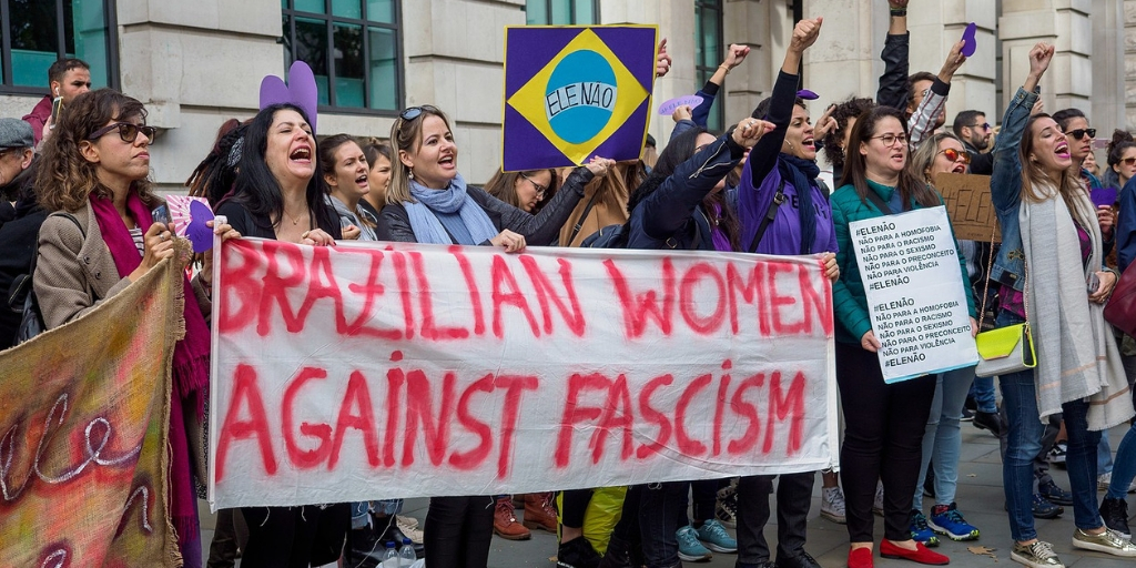 "A group of Brazilian women hold up a white sign that says ""Brazilian women against fascism"" in pink paint."