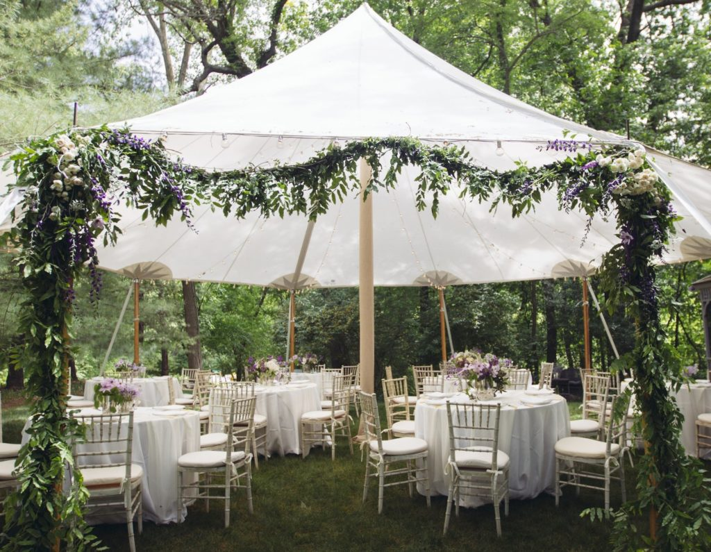A party venue is set up outside around trees. There is a white tent with all white table settings.