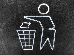 A chalk figure of a person throwing away a piece of trash in a trash can.