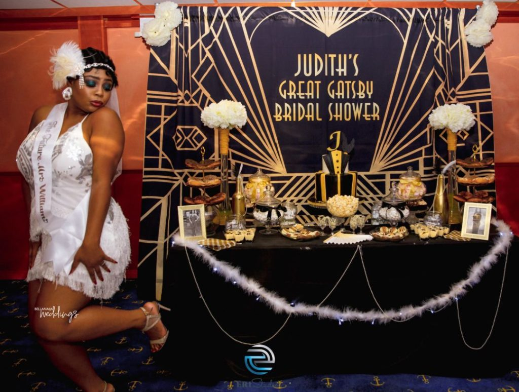 A woman wearing a white flapper dress stands net to a black and gold table display and the banner reads Judith's Great Gatsby Bridal Shower.