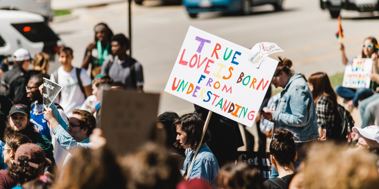 A protest taking place with a sign that states 'True Love is Born From Understanding' in multicolors