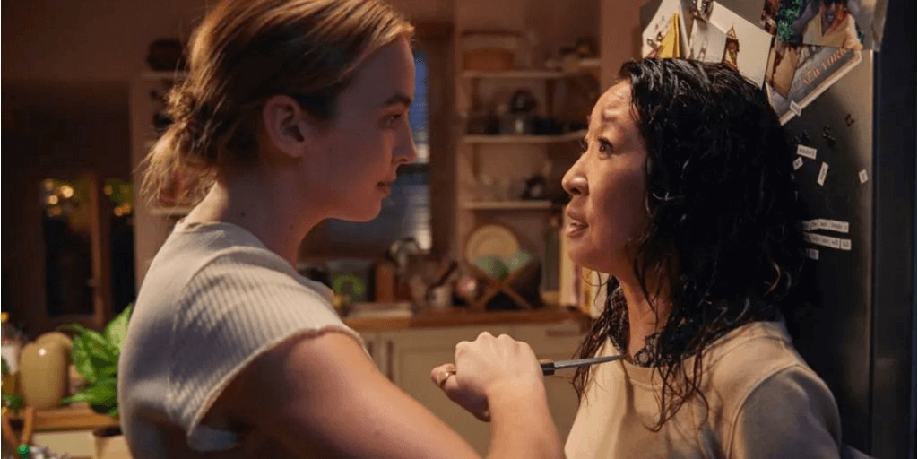 [Image description: A woman holds a weapon against another woman.] Via BBC AMERICA