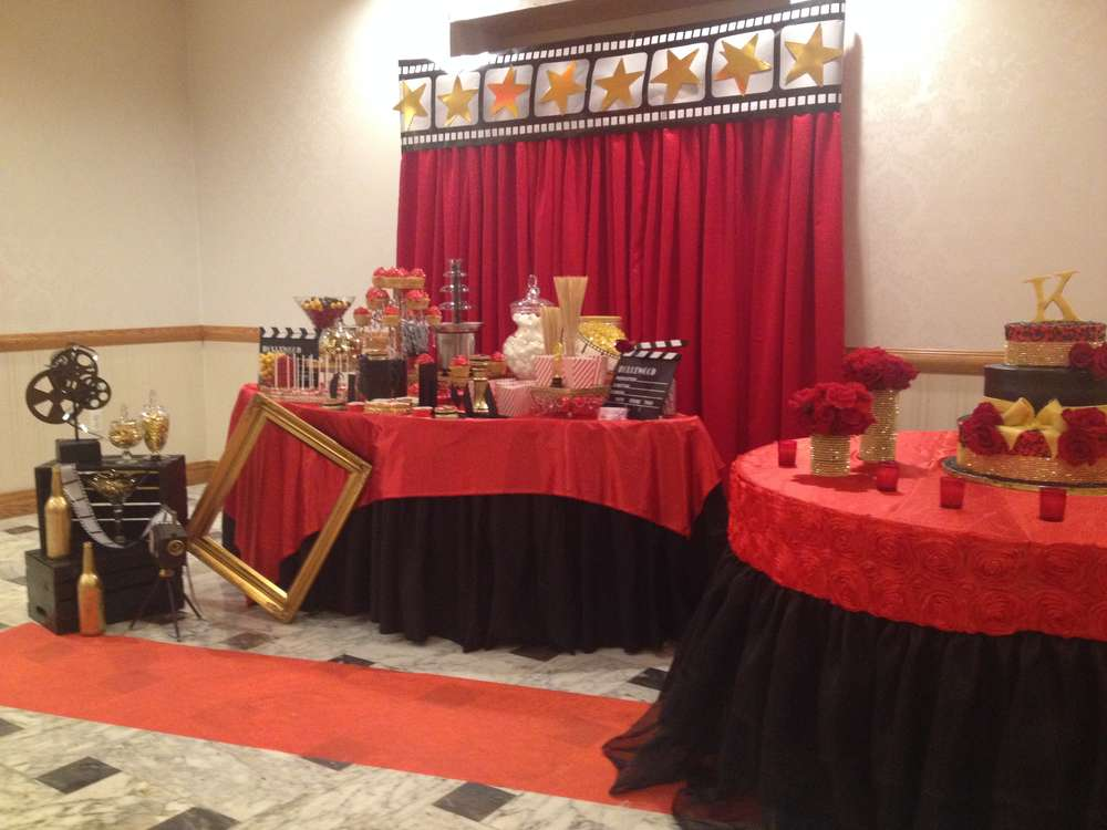 Party set up with a red carpet theme, red and black backdrop and table covers, a picture frame and movie themed trinkets.