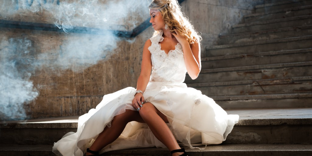 A bride wearing a white wedding dress sits on steps next to graffiti with her dressed puller up to her knees.