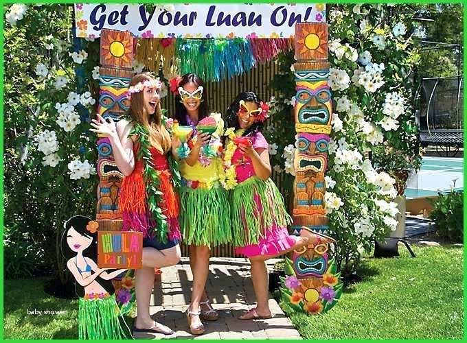 Three women send in front of a flower wall outside surrounded by tiki-styled decor wearing grass skirts and luaus.