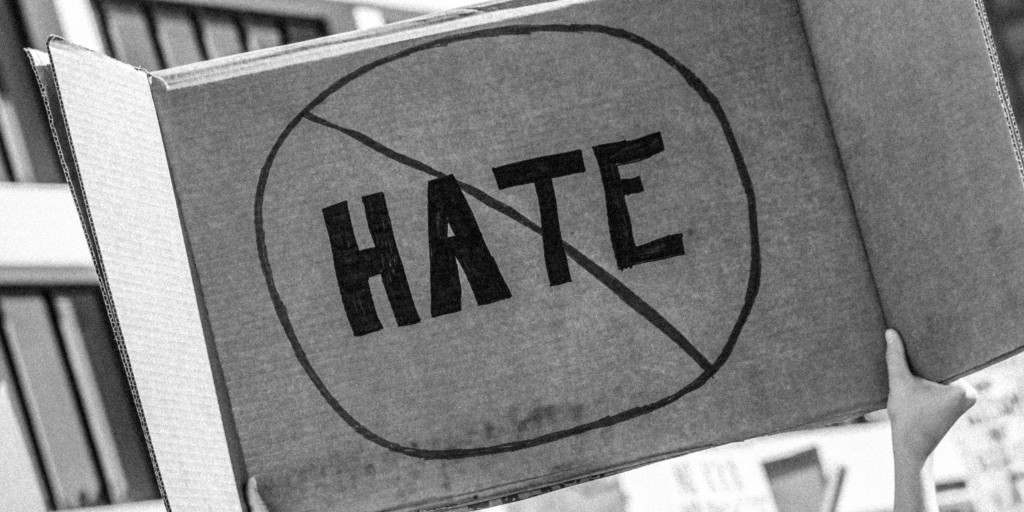 The word 'HATE', written on a large piece of paper in a circle, crossed out]