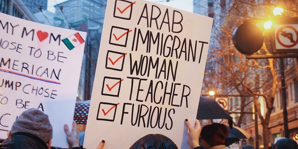 "A woman holds up a sign reading, ""Arab, immigrant, woman, teacher, furious,"" at a rally."