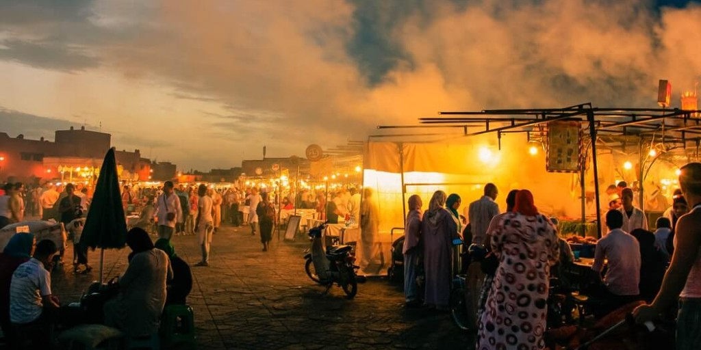 A glowing bazaar during the evening with crowds of people at stalls and the bluish white sky is covered with smoke.
