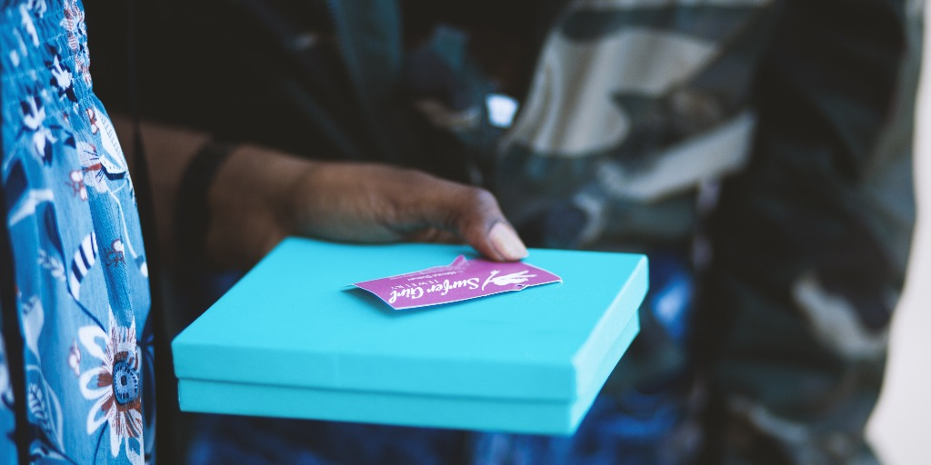 Hands holding a blue gift box with a gift voucher.