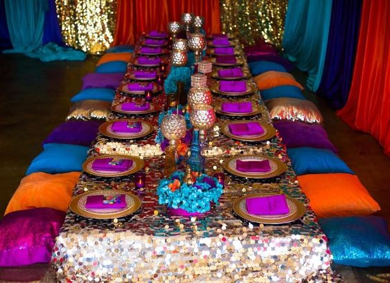 A table is set up on the ground, with a sequence table cover and blue and purple pillows on the floor for seating.