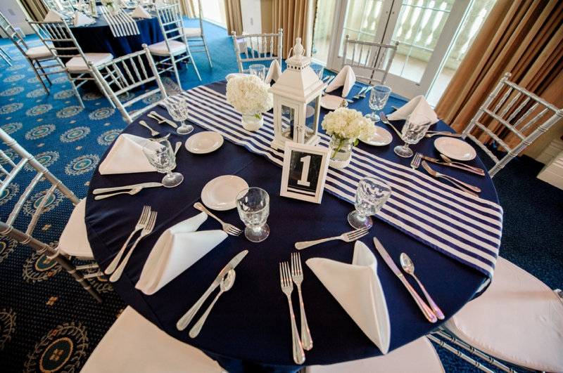 A table setting with a navy blue cover and white napkins and nautical design.